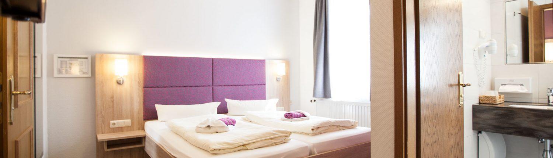 Foto Blick in ein Hotelzimmer mit Doppelbett und Ausschnitt des Duschbads